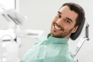 a young male patient sitting in the dentist chair