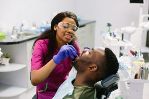 a male patient having his teeth checked by a dental hygienist