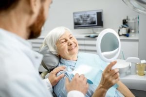 An older woman looking at her new smile in the mirror after receiving dental implants in Richardson