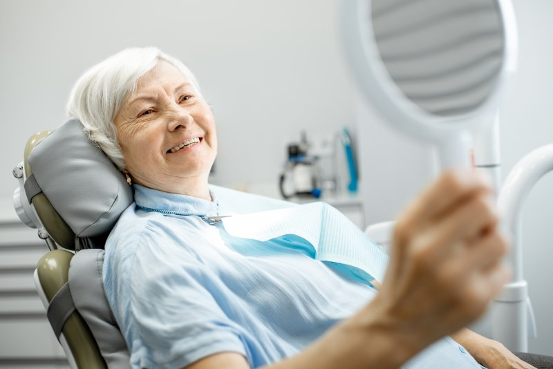 an older woman looking at her dental implants in the mirror while seated in the dentist's chair