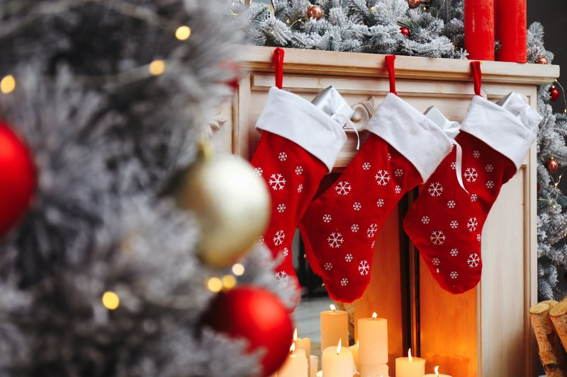 an image of three stockings hanging over the fireplace and a Christmas tree