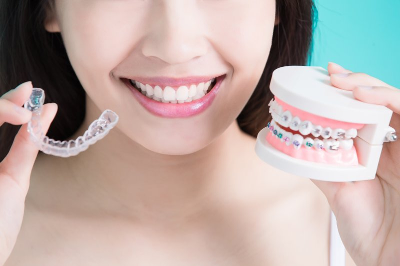 a young woman holds an Invisalign aligner and a mouth mold with traditional braces