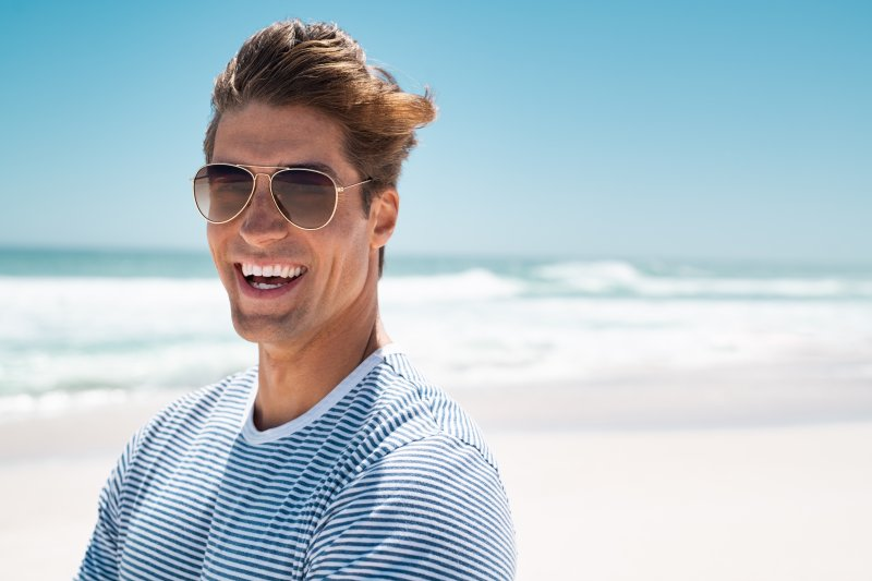 a young man wearing sunglasses and showing off his smile after having his teeth whitened by a dentist in Richardson
