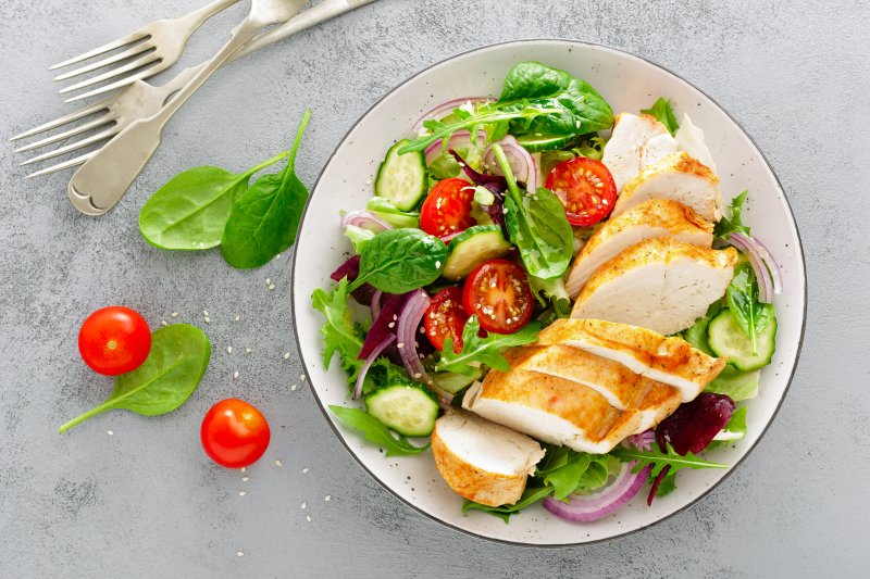 a plate full of salad greens and grilled chicken